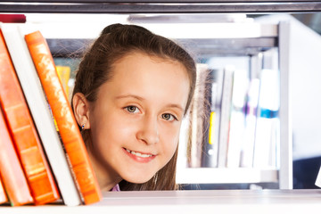 Beautiful girl looks through bookshelf portrait