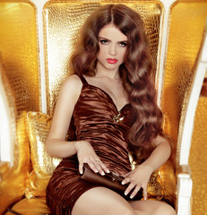 Glamorous woman with long hair sitting in luxurious golden armch