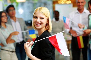 Cheerful businesswoman holding flag of Poland