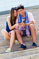 Young couple having fun with smartphones, outdoors