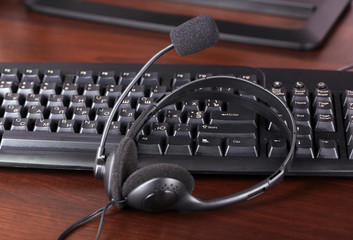 Headphone and keyboard close-up on wooden desk background