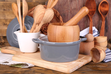 Composition of wooden cutlery, pan, bowl and cutting board