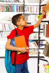 Boy searching books on library bookshelf
