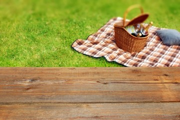 Picnic table, blanket and basket in the grass