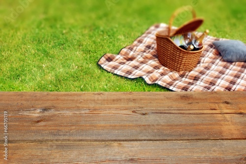 Plexiglas Picknick Picnic table, blanket and basket in the grass