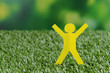 Paper people on green grass, close up