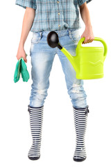 Young woman in rubber boots holding watering can, isolated