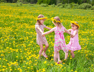 Children playing on a dandelion field