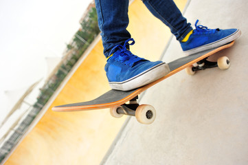 woman skateboarder legs skateboarding at skatepark