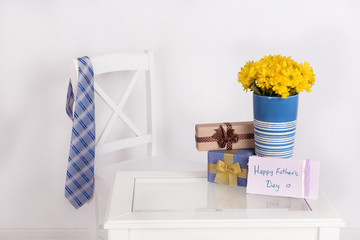 Bouquet of flowers, gift boxes and tie on Fathers Day in room
