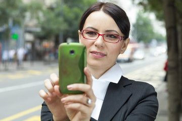 business woman taking a picture with mobile phone