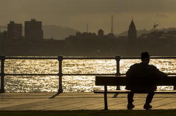 Anciano sentado frente al mar