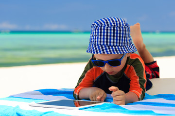 little boy playin on touch pad at the beach