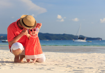 father and baby having fun on the beach