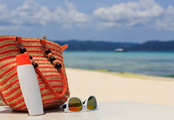 bag, sun glasses and suncream on tropical beach
