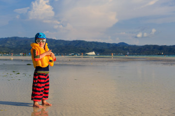 little boy in life jacket on the beach