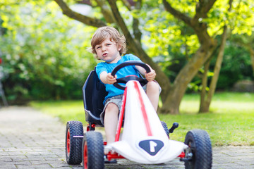 Active little boy having fun and driving toy car