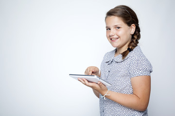 Happy child with tablet computer against gray background