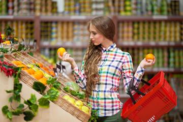 Молодая девушка выбирает фрукты в магазине