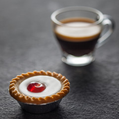 Small cherry cake with a glass of fresh espresso