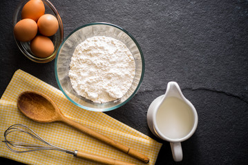 Baking ingredients - flour, milk, eggs with a whisk,
