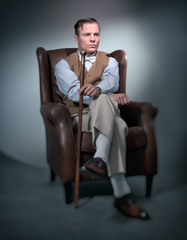 Retro classic business fashion man sitting in big leather chair.