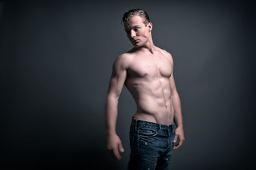 Healthy good looking young muscled fitness man wearing blue jean