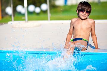 Мальчик у бассейна в солнечных очках