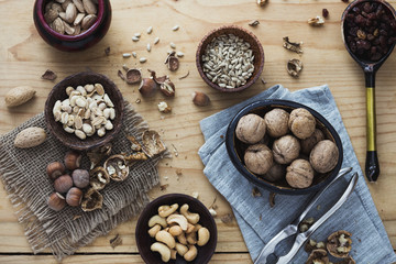 Nuts, dried fruits and seeds on wooden background