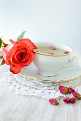 Cup of tea with dried roses and fresh rose