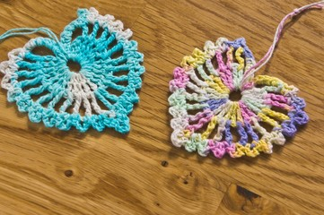 Crochet two hearts on a wooden table