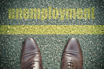 concept pied sur la route et message - unemployment (chômage)