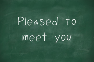 Pleased to meet you handwritten on blackboard