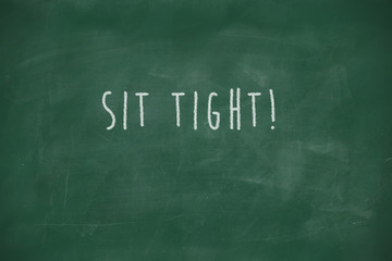 Sit tight handwritten on blackboard
