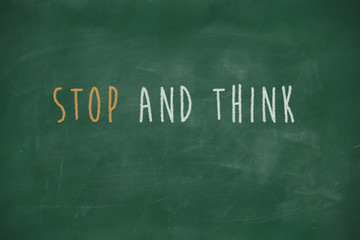 Stop and think handwritten on blackboard