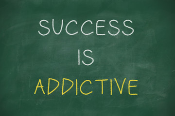 Success is addictive handwritten on blackboard