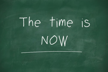The time is now handwritten on blackboard