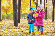 Little boy and little girl stand in autumn park, boy eats stick