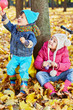 Children sit leaning at tree trunk in autumn park