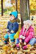 Little children sit leaning at tree trunk in autumn park