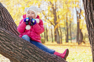 Little girl with binocular sits on inclined tree trunk in autumn