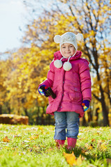 Little girl with binocular stands on grassy glade in autumn park