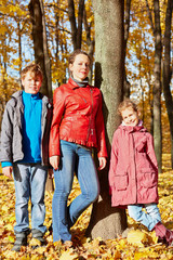 Mother stands with her two children leaning to tree trunk