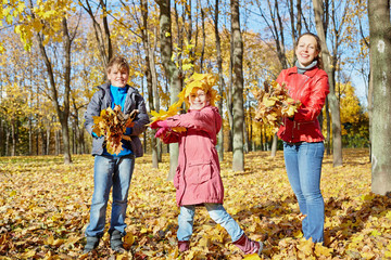 Mother and two children play with yellow fallen leaves