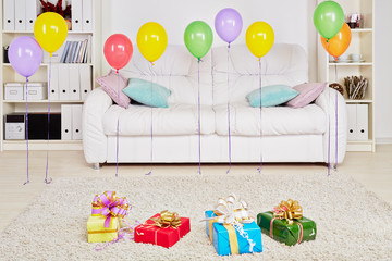Room with sofa, gift boxes on floor and birthday air balloons