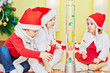 Three children in santa caps sit on fur rug and look