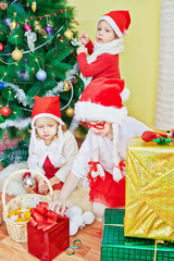 Two little girls in santa caps with strings