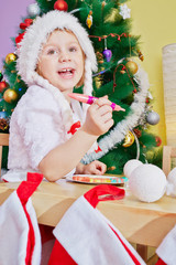 Little girls in santa cap plays in food sitting at wooden table