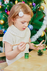 Little girl paints revealed pine-cone with green gouache sitting