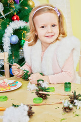 Smiling little girl dressed in furry mantle sits at wooden table
